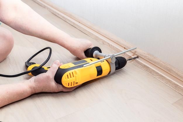 Las manos femeninas sostienen una herramienta de perforación pesada y hacen un agujero en la pared para fijar el zócalo