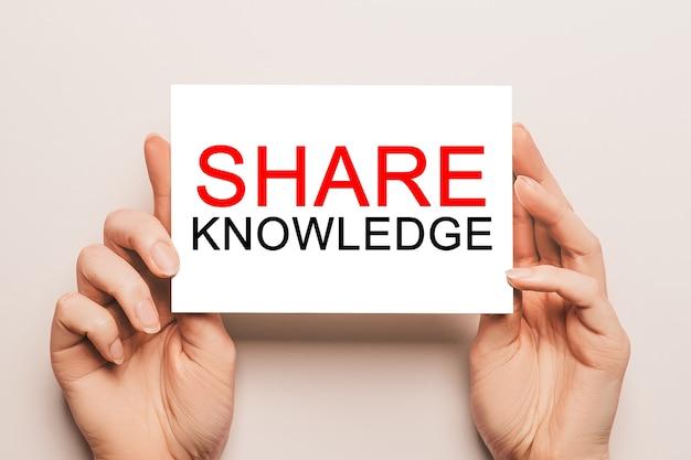 Manos femeninas sostienen papel de tarjeta con el texto compartir conocimientos sobre un fondo amarillo. concepto de negocios y finanzas