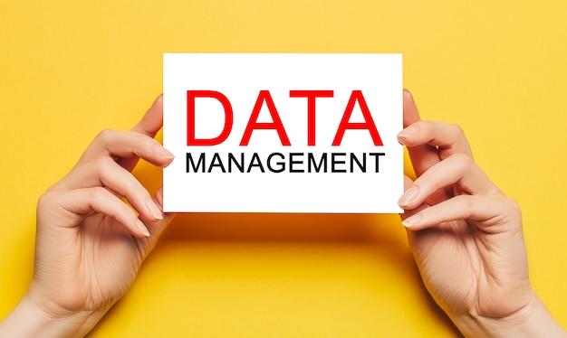Las manos femeninas sostienen el papel de la tarjeta con el texto gestión de datos sobre un fondo amarillo. concepto de negocios y finanzas