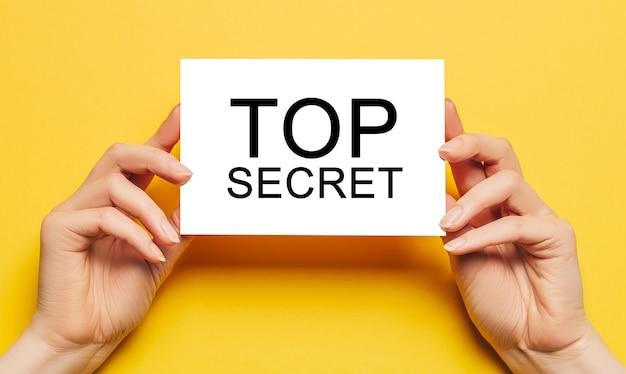 Manos femeninas sostienen papel de tarjeta con texto top secret sobre un fondo amarillo. concepto de negocios y finanzas