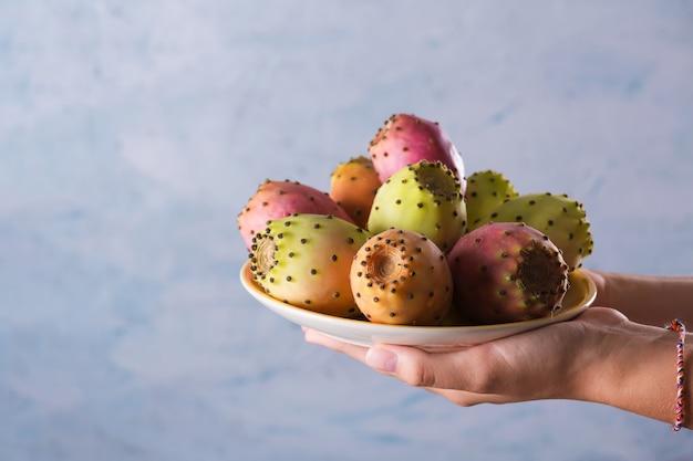 Manos femeninas sostienen un plato con frutas frescas maduras de nopal sobre un fondo gris