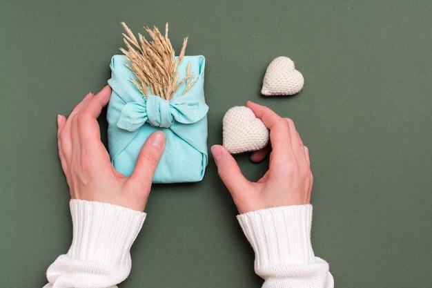 Manos femeninas sostienen regalo furoshiki ecológico con espigas de hierba seca y dos corazones tejidos sobre un fondo verde
