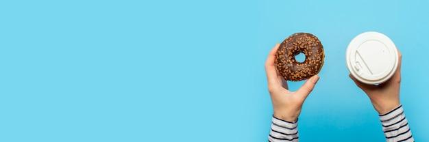Las manos femeninas sostienen una rosquilla y una taza de papel con café en un azul. concepto de confitería, pastelería, cafetería.