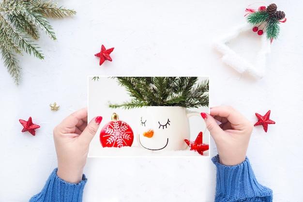 Manos femeninas sostienen una tarjeta de felicitación de navidad en el fondo de una mesa blanca con decoración navideña.