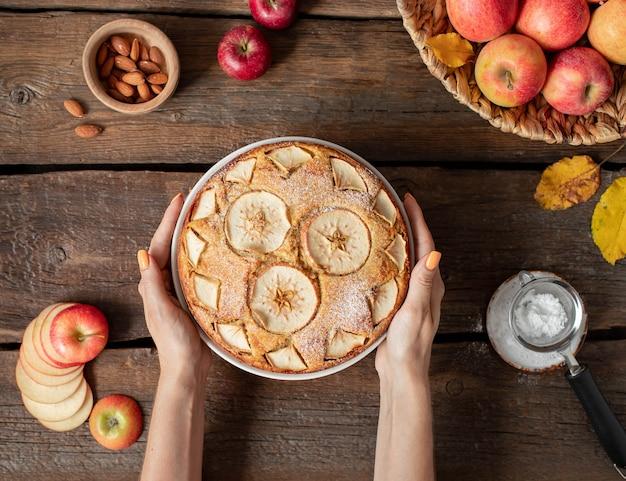 Manos femeninas sostienen tarta de manzana con azúcar en polvo, vista superior, en madera oscura