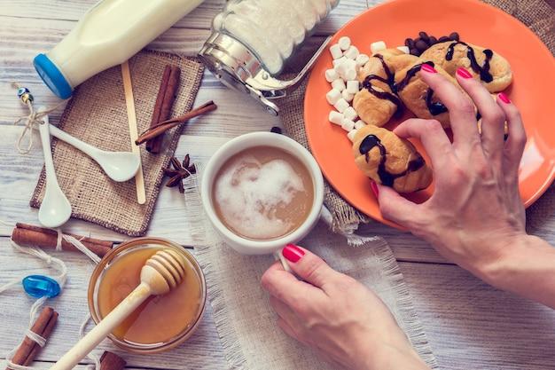 Manos femeninas sostienen una taza de café y croissants.