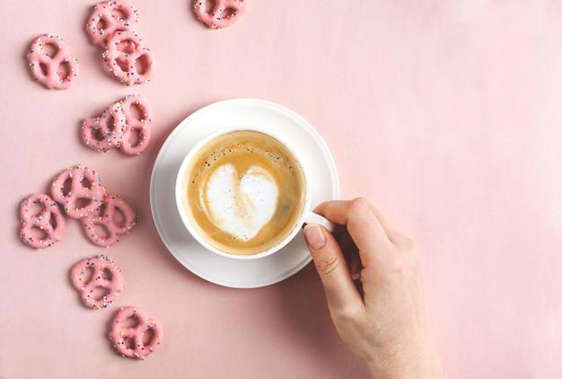 Manos femeninas sostienen la taza de café con forma de corazón de arte. concepto de amor vista plana, vista superior