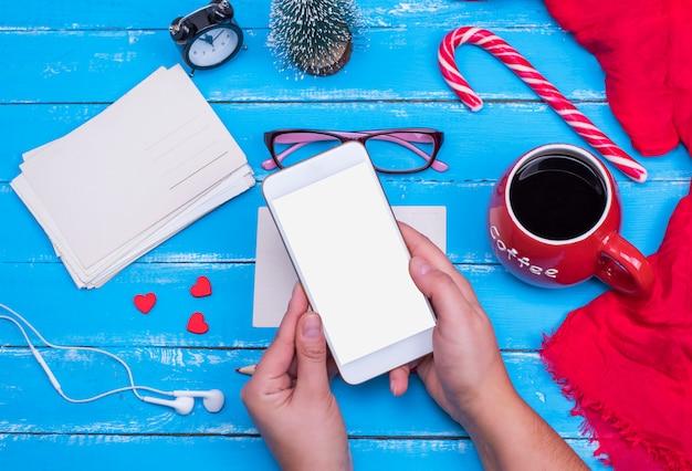Manos femeninas sostienen un teléfono inteligente blanco con una pantalla en blanco
