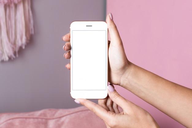 Manos femeninas sostienen teléfono móvil con maqueta de pantalla blanca sobre una superficie interior rosa