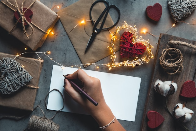 Manos femeninas con tarjeta de regalo y caja de regalo. la niña firma una postal para el día de san valentín. regalo, romance, sorpresa