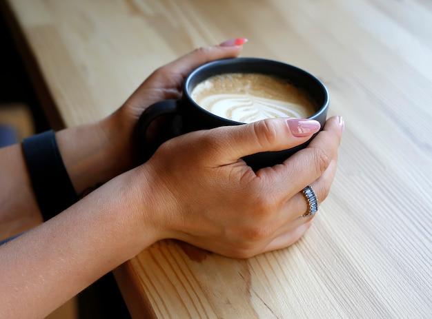 Manos femeninas con taza de café