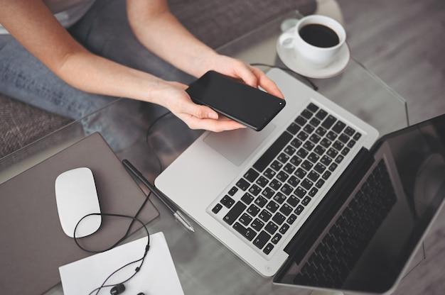 Manos femeninas con teléfono inteligente en el lugar de trabajo interior, mujer de negocios independiente que usa el teléfono celular en el escritorio de la oficina, trabajando desde casa con teléfono inteligente y computadora portátil cuarentena remota de trabajadores