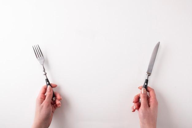 Manos femeninas con tenedor y cuchillo en blanco