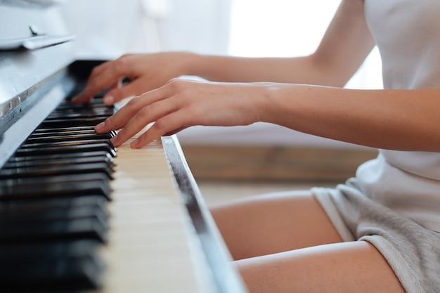 Manos femeninas tocando teclas negras y marfil mientras toca música clásica en el piano en casa