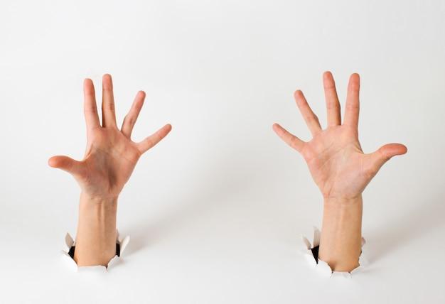 Manos femeninas a través de los agujeros rasgados de un papel blanco