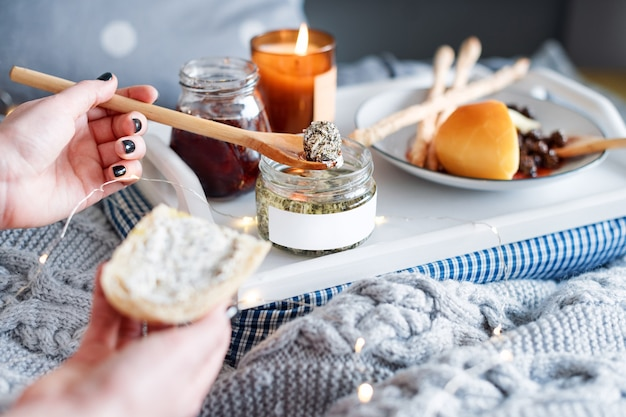 Manos femeninas untando queso crema en pan fresco