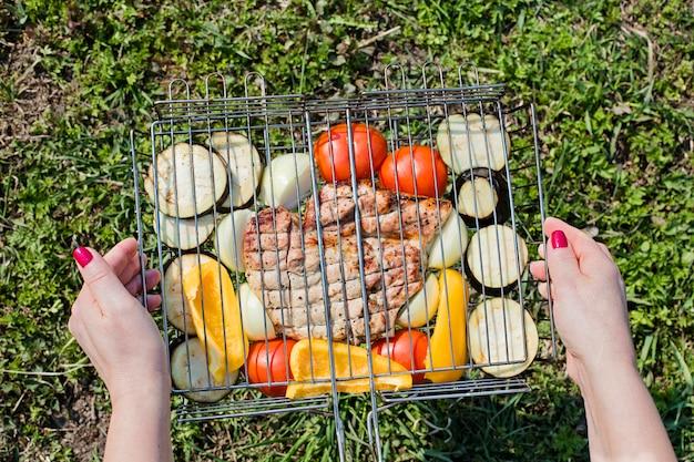 Manos femeninas con verduras apetitosas y filete de cerdo sobre una rejilla