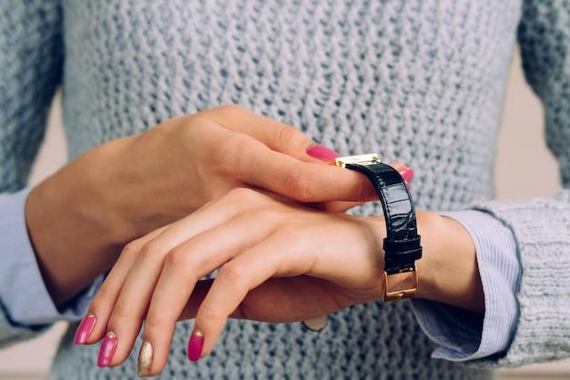 Las manos femeninas con un vestido de manicura brillante miran en la muñeca