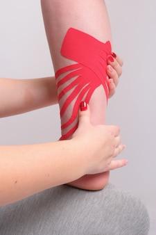 Las manos del fisioterapeuta aplicando cinta de kinesio en la pierna de la mujer de cerca. vista vertical