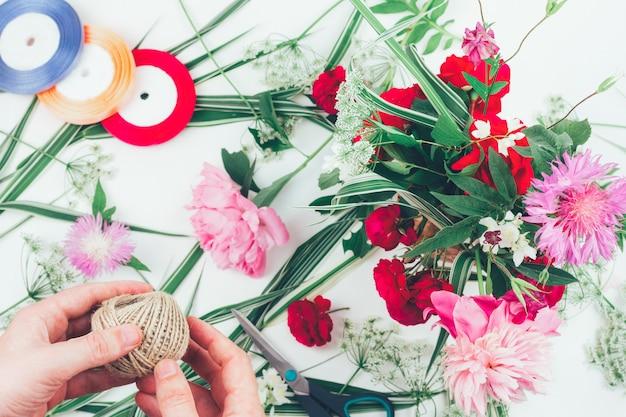 Las manos de un florista masculino haciendo una bella composición de flores.