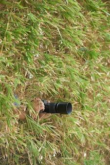 Manos del fotógrafo irreconocible escondido en la espesa vegetación y sosteniendo la cámara