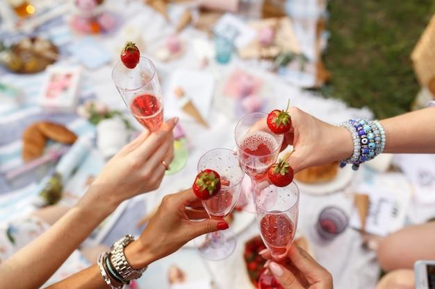Manos con gafas vítores en día de verano picnic.
