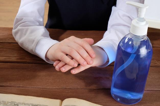 Manos y gel antibacteriano sobre la mesa. una niña trata sus manos con un antiséptico.