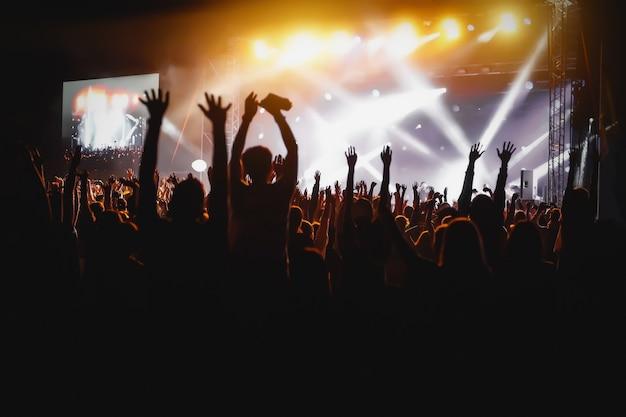 Manos de gente feliz multitud divirtiéndose en el escenario del festival de rock en vivo de verano
