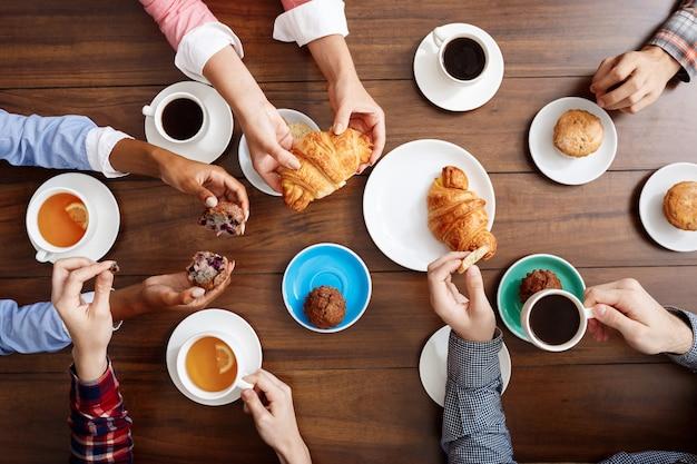 Manos de la gente en la mesa de madera con cruasanes y café.