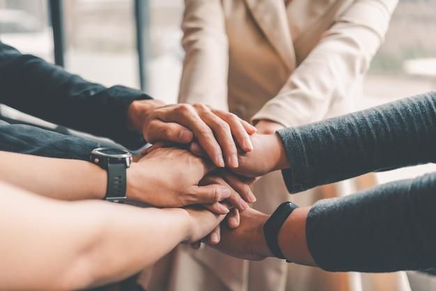 Las manos de la gente de negocios se juntan en una pila de manos para simbolizar la colaboración, el trabajo en equipo para alcanzar las metas y el éxito.