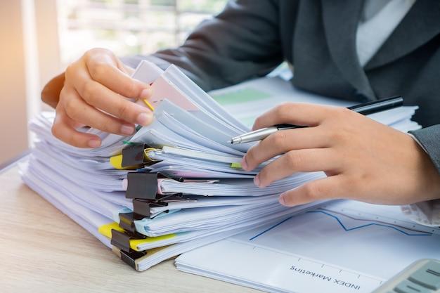 Manos gerentes de negocios mujeres jóvenes comprobando la disposición de la pila de documentos sin terminar