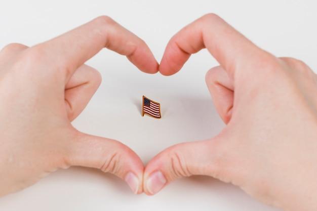 Manos gesticulando corazón y bandera americana