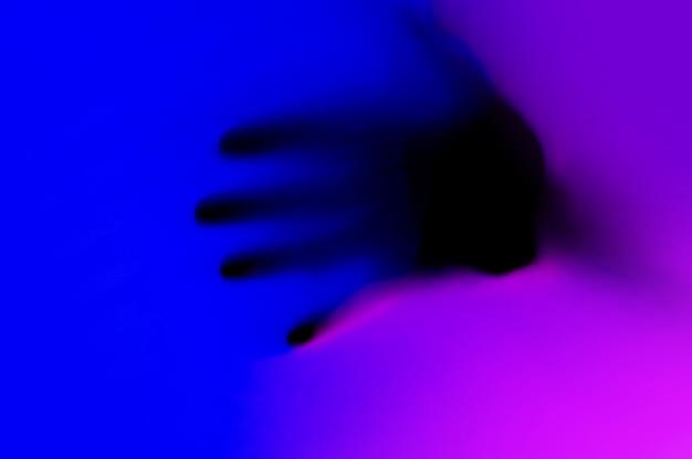 Manos en gradiente de luz de neón azul y rosa detrás de la superficie blanca.