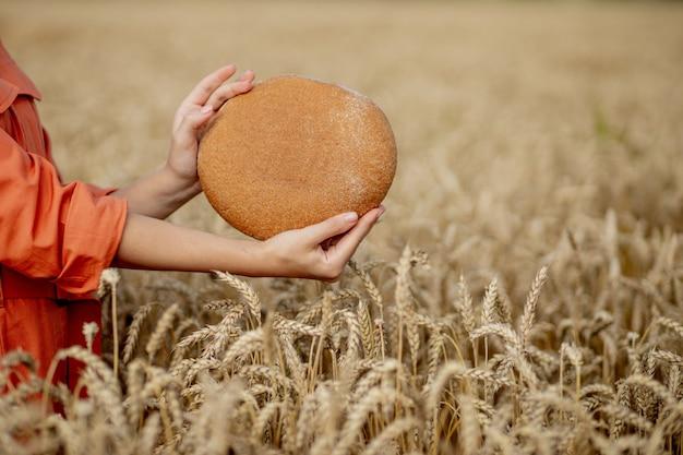 Manos de granjero con pan de salvado recién horneado