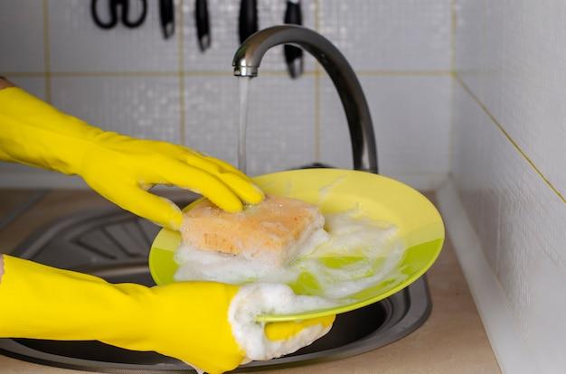 Manos en guantes amarillos de un plato con esponja jabonosa.
