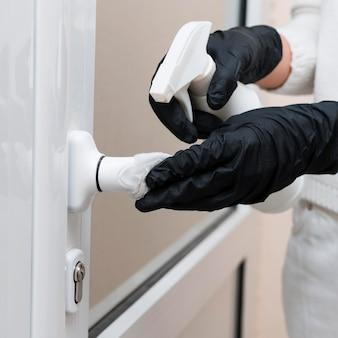 Manos con guantes desinfectando la manija de la puerta
