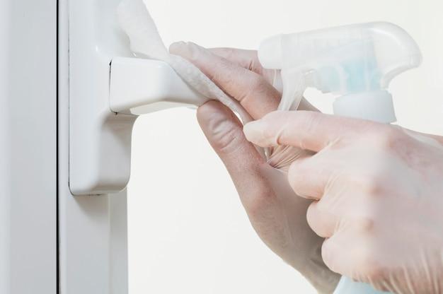 Manos con guantes desinfectando la manija de la ventana