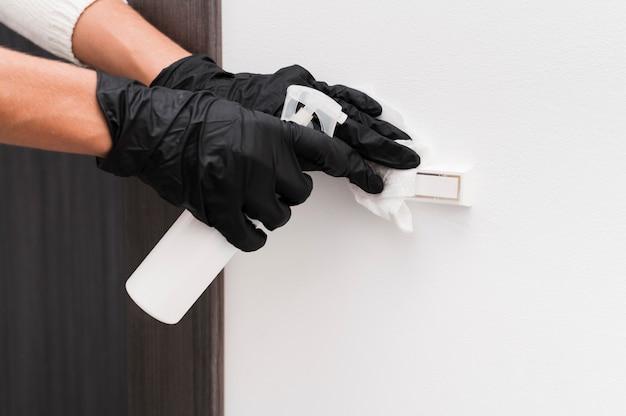 Manos con guantes desinfectando el timbre de la puerta