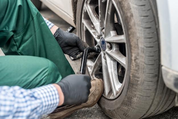 Manos en guantes, fijación de tuercas en rueda de coche closeup