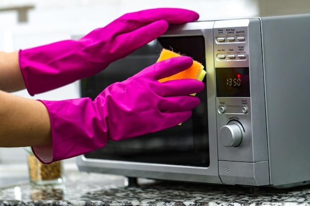 Manos en guantes de goma limpiando un microondas con una esponja