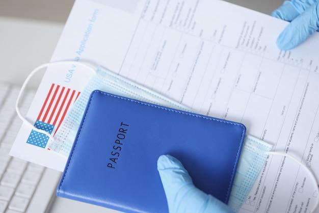Manos en guantes de goma con pasaporte y documentos para primer plano de visa de estados unidos. dificultad para viajar