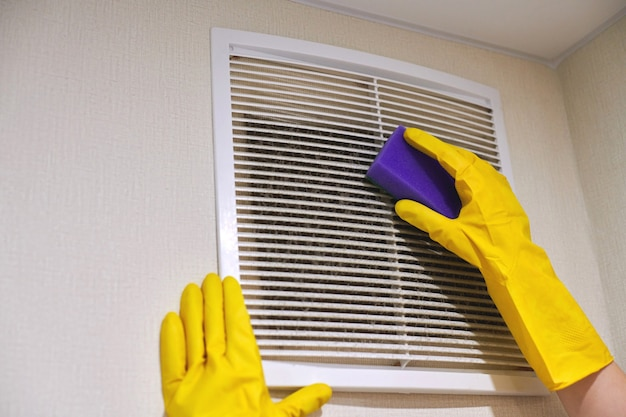 Manos en guantes de goma protectores limpiando rejilla de ventilación de aire polvoriento de hvac