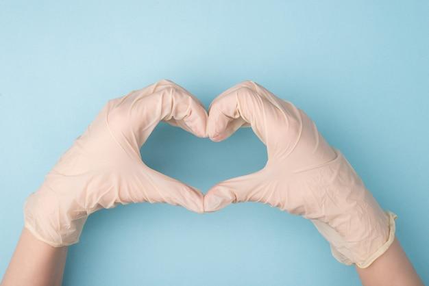 Manos en guantes haciendo forma de corazón con dedos aislados