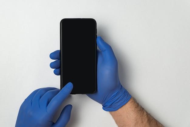 Manos en guantes médicos azules con smartphone en blanco