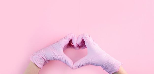 Las manos con guantes médicos son de color rosa en forma de corazón sobre un fondo rosa