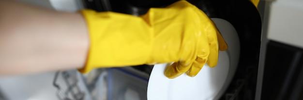 Las manos en guantes ponen el plato a los platos en el lavavajillas