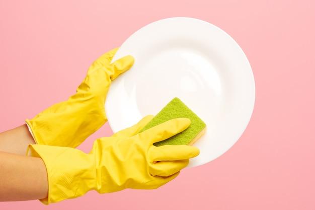 Manos en guantes protectores amarillos lavando un plato