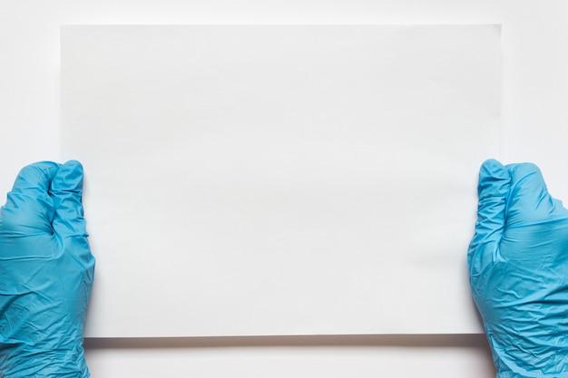 Manos en guantes protectores azules con blanco hoja de papel en blanco