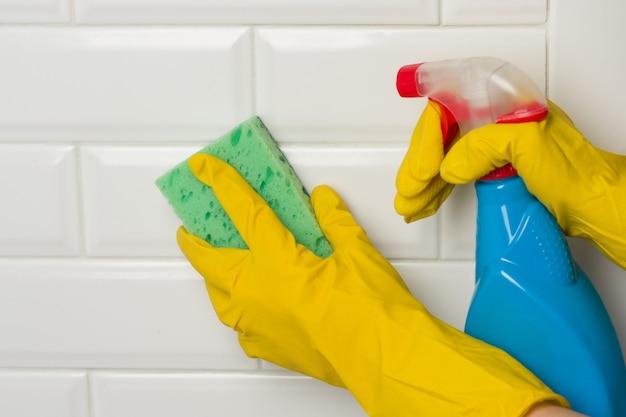Manos en guantes protectores de goma con detergente y esponja