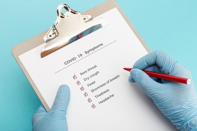 Manos con guantes protectores sosteniendo una lista de verificación en el portapapeles con síntomas de covid-19